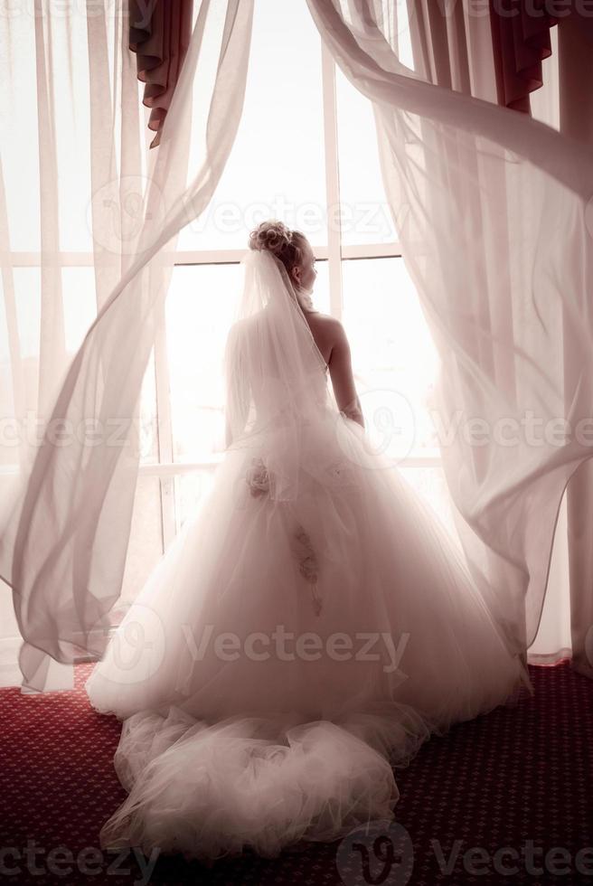 sposa in piedi accanto a una grande finestra foto
