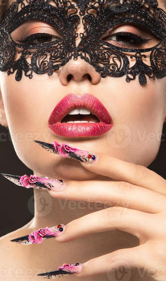 bella ragazza in maschera con unghie lunghe e labbra sensuali foto