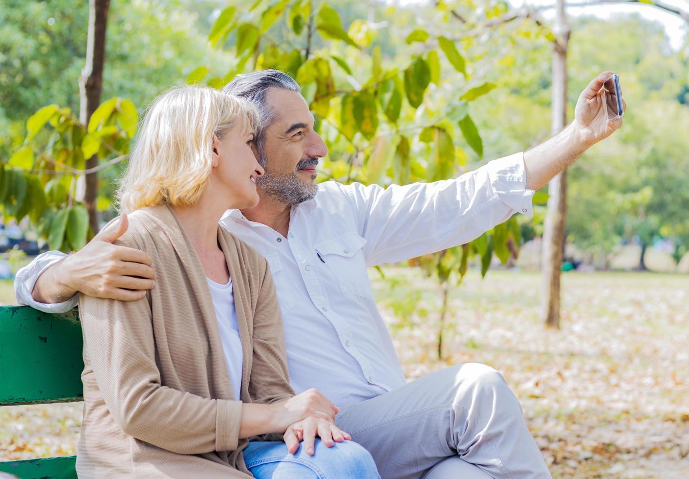 coppia che cattura selfie in un parco foto