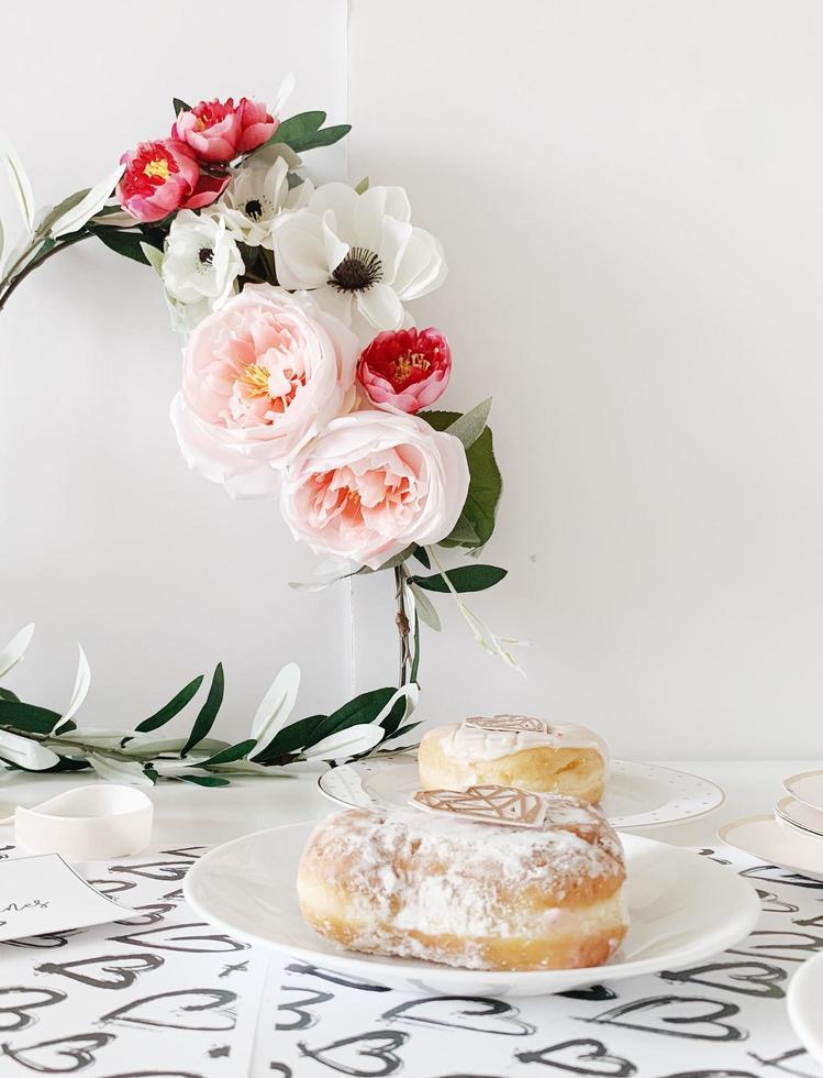due ciambelle su piatti in ceramica bianca foto