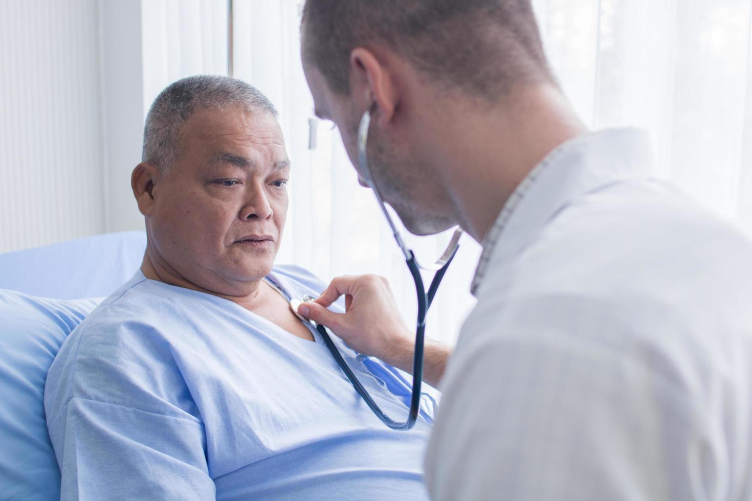 medico utilizzando uno stetoscopio per ascoltare il cuore del paziente foto