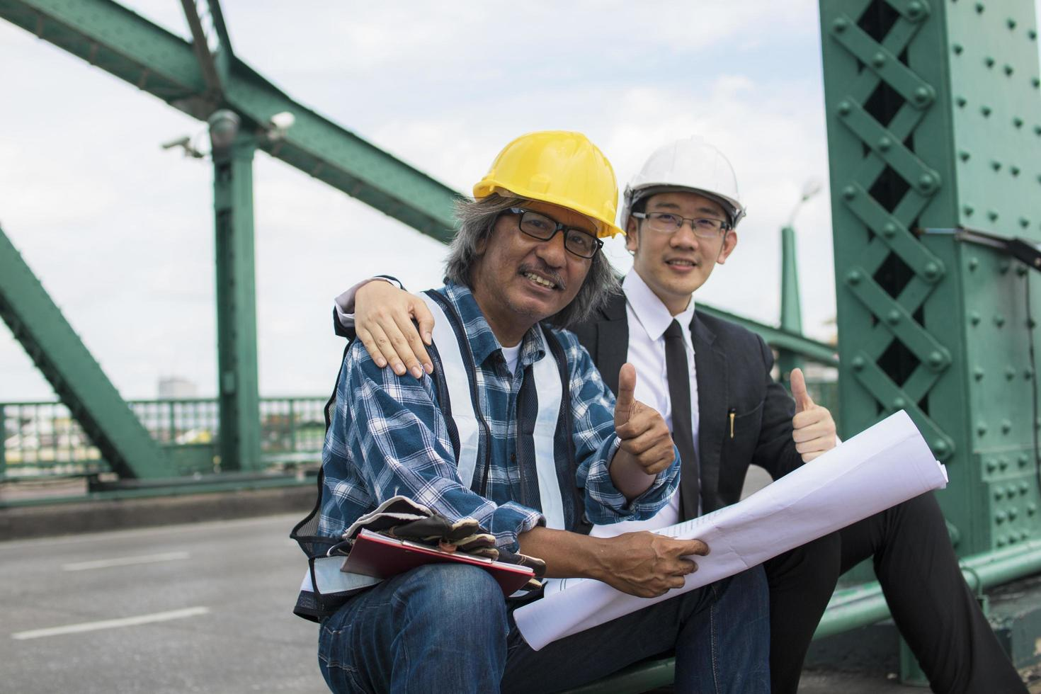 un appaltatore e un ingegnere che danno i pollici in su foto