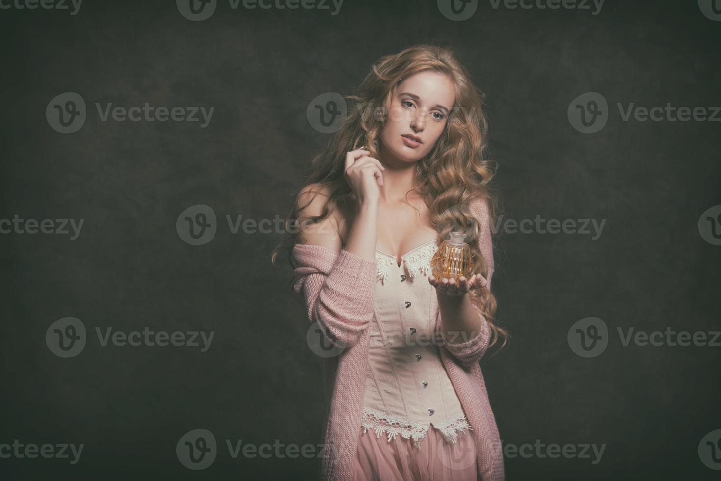 donna moda vintage che tiene vecchia bottiglia di profumo. indossa un cardigan rosa. foto