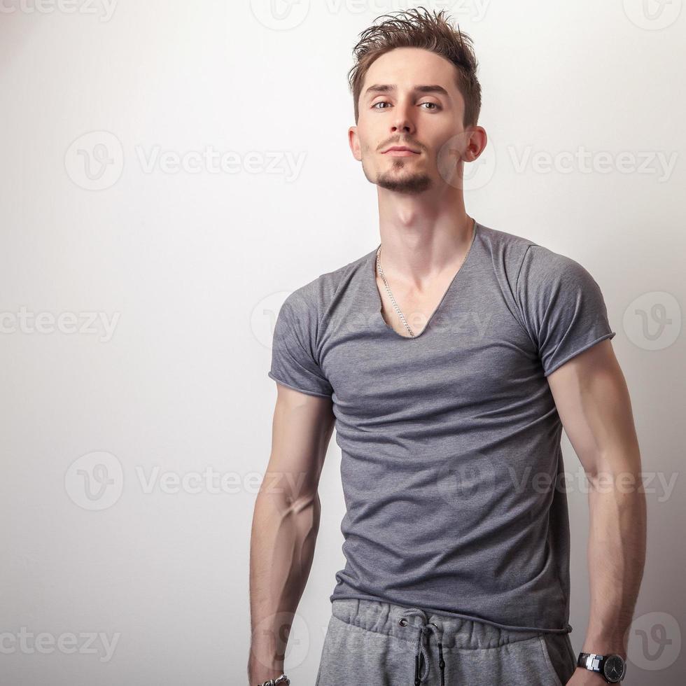 giovane uomo bello in maglietta grigia. foto
