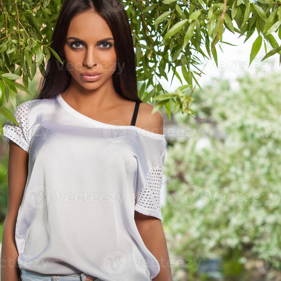 ragazza bruna in camicia di seta bianca in posa nel giardino estivo. foto