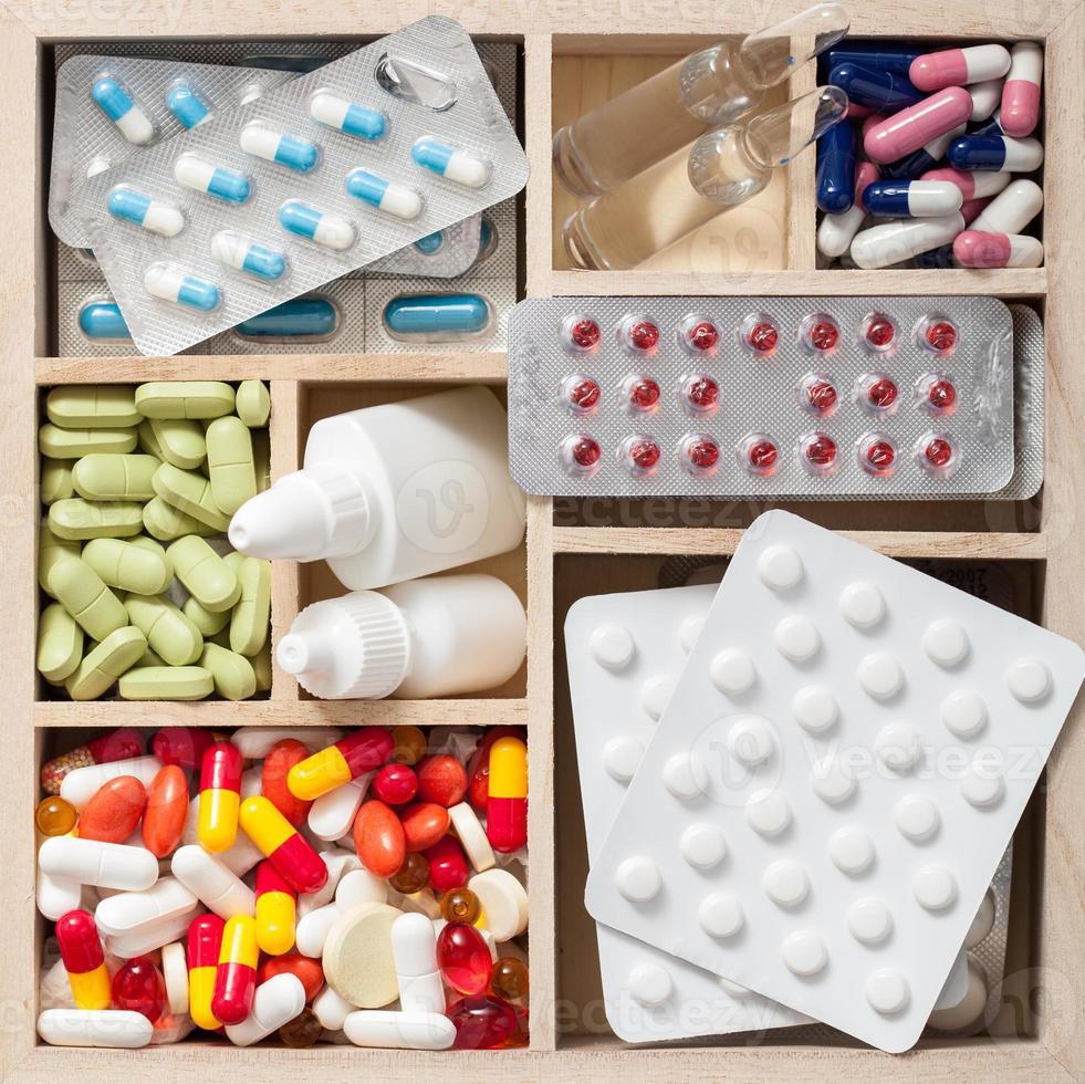 pillole mediche e fiale in scatola di legno foto