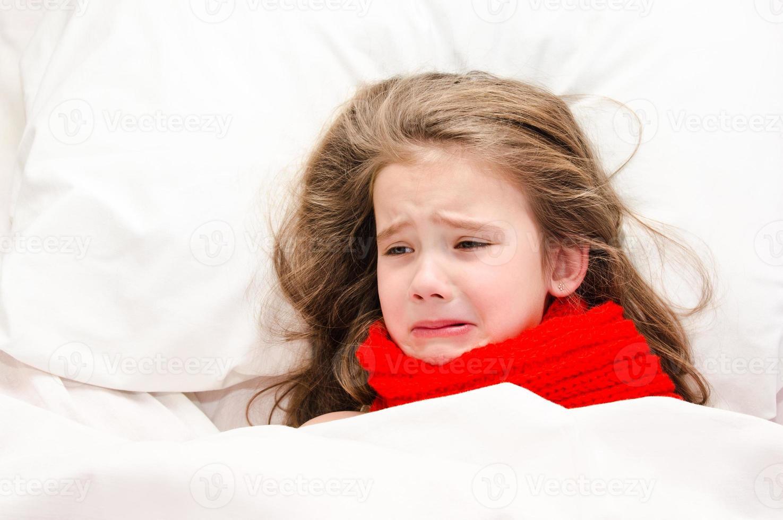 bambina malata sdraiata nel letto in sciarpa rossa foto