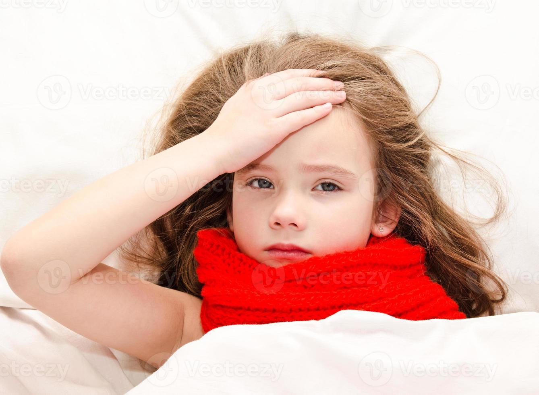 bambina malata sdraiata nel letto foto