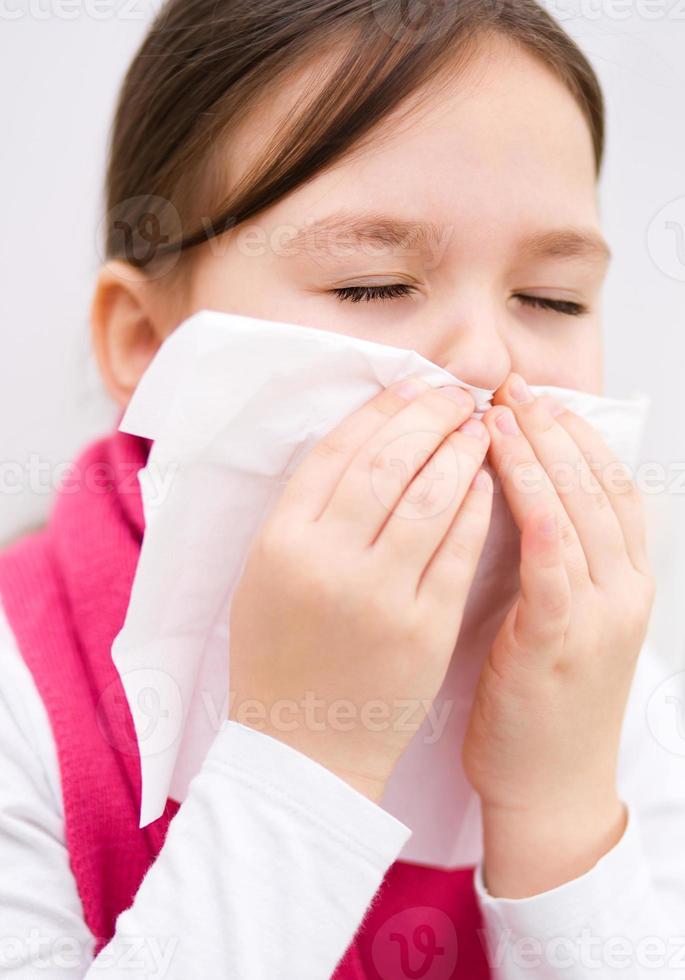 la ragazza si sta soffiando il naso foto