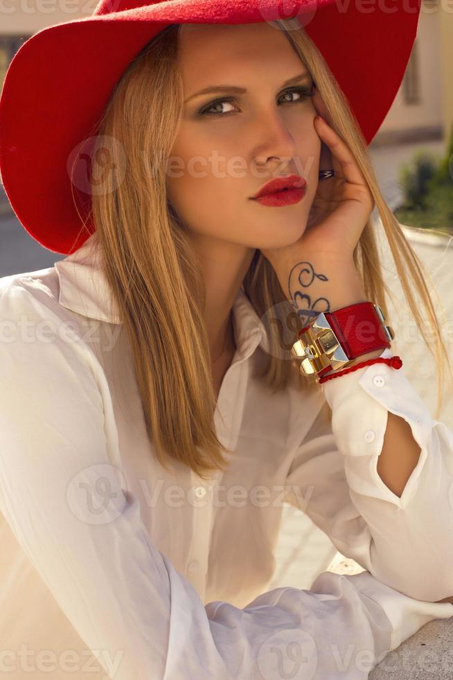bella ragazza con i capelli biondi in un elegante cappello rosso foto