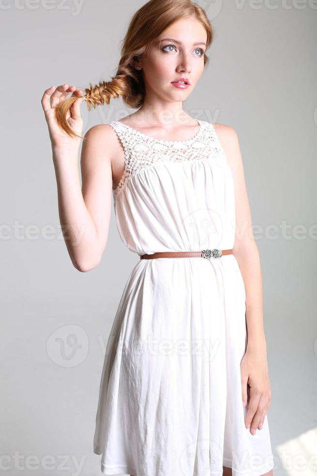 ragazza con i capelli rossi e le lentiggini in un elegante abito bianco foto