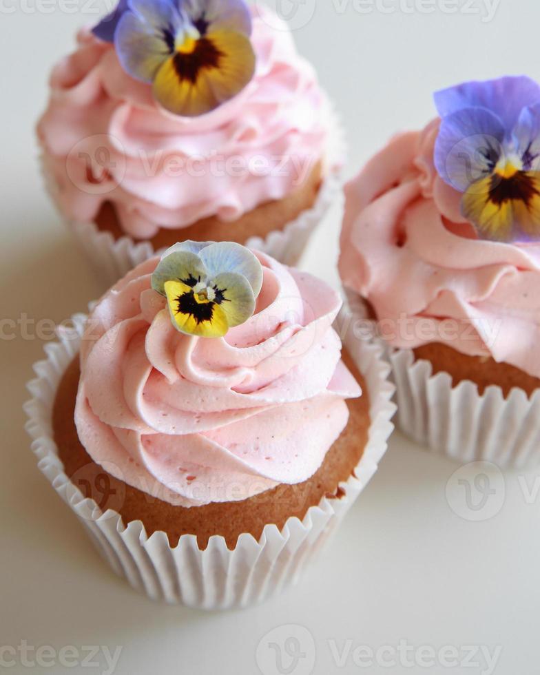 cupcakes alla vaniglia con glassa rosa fatti in casa con fiori commestibili foto