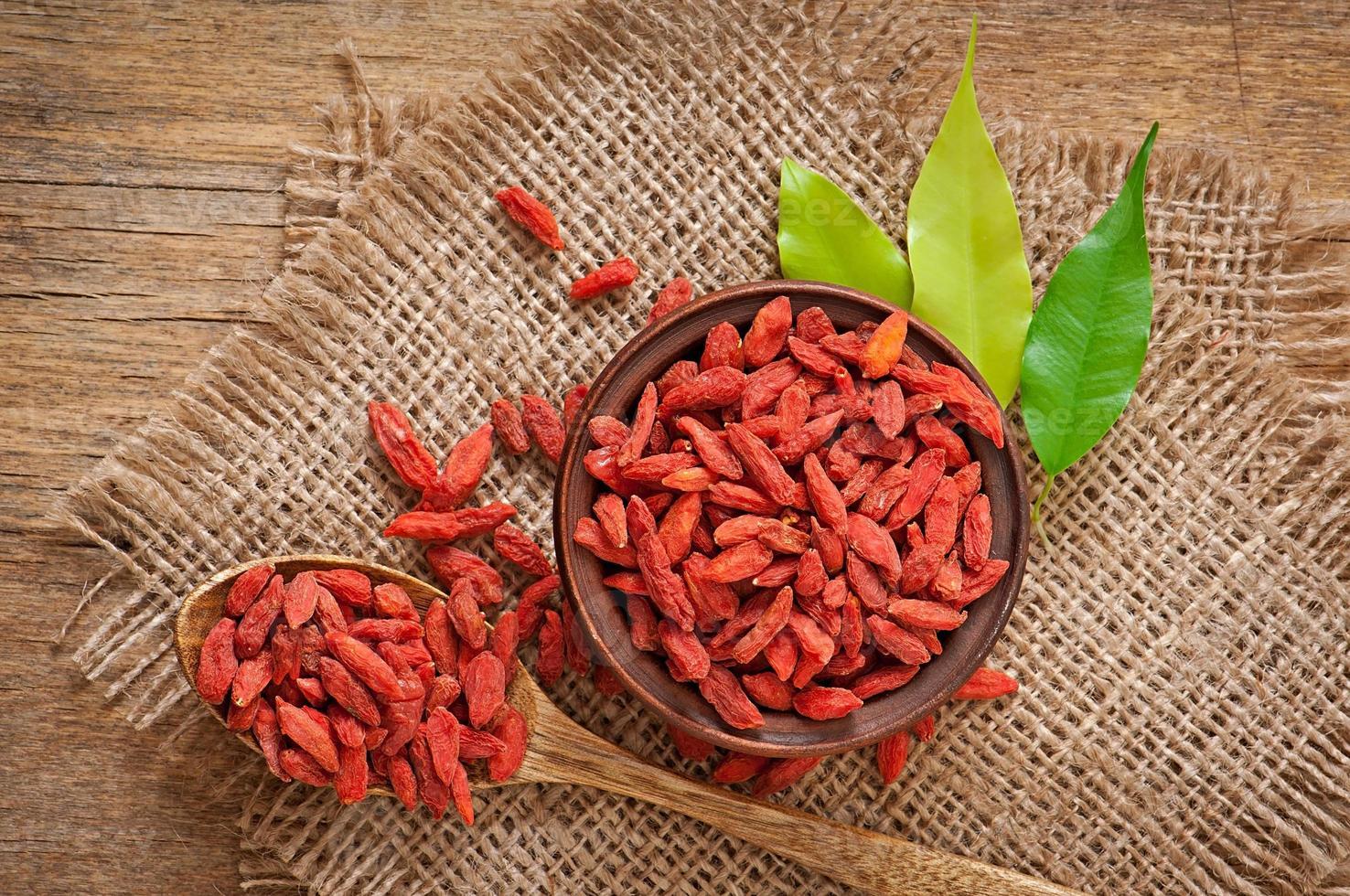 bacche di goji essiccate rosse in un cucchiaio di legno foto
