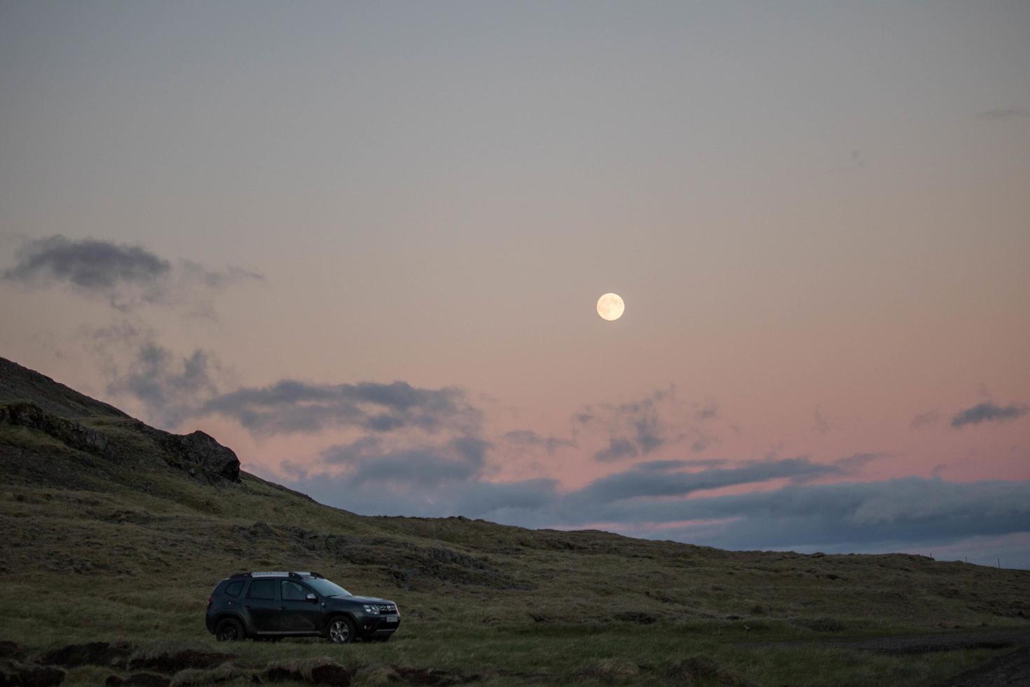 macchina parcheggiata sul campo erboso al tramonto foto