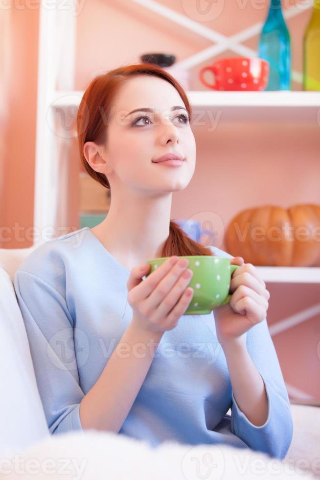 d ragazza in camicetta blu con tazza verde foto