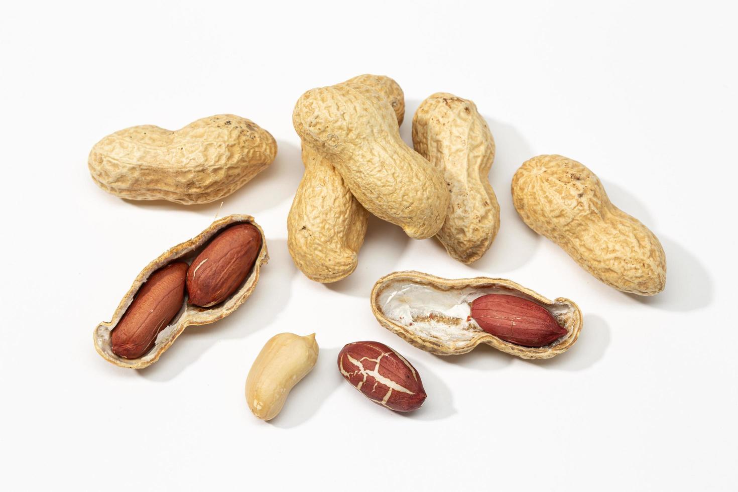 arachidi con gusci su uno sfondo bianco foto
