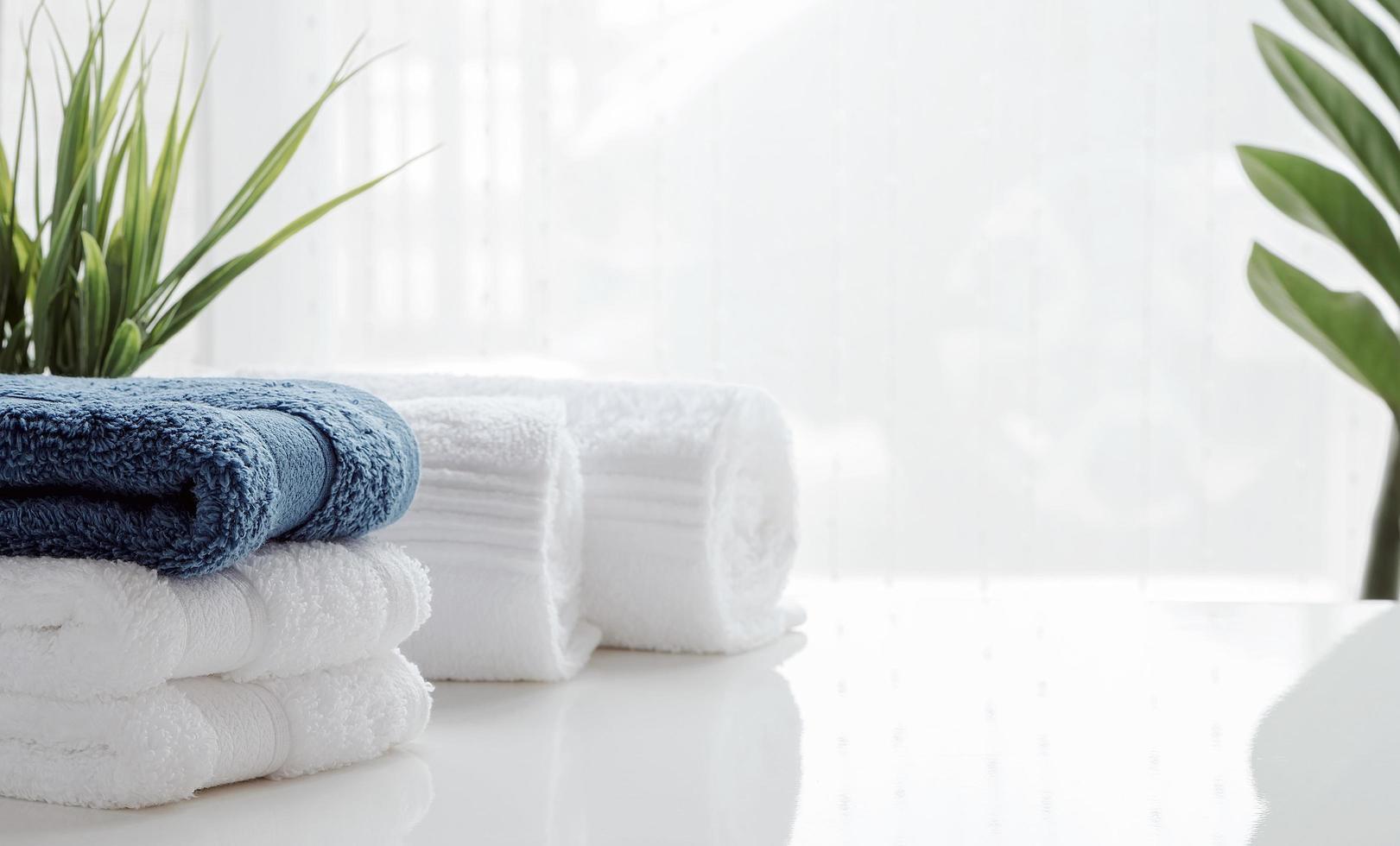 asciugamani puliti e piante d'appartamento su un tavolo bianco foto
