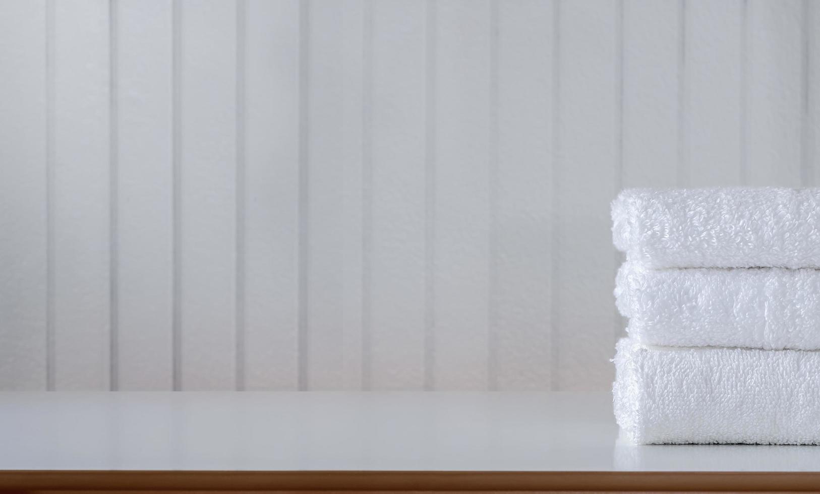pila di asciugamani bianchi piegati su un tavolo foto