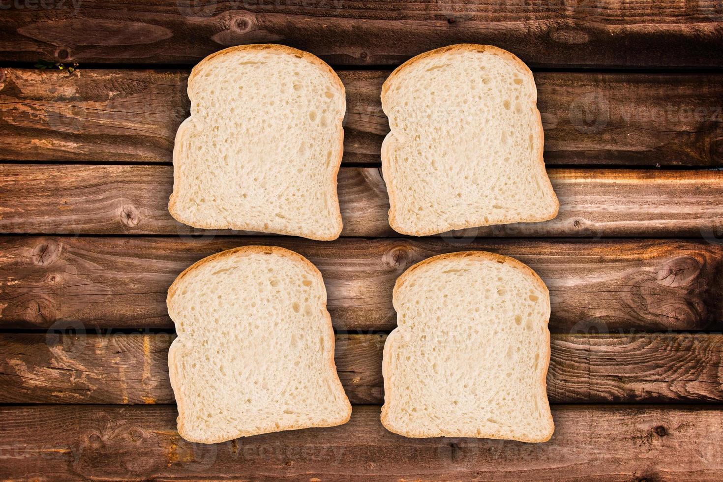 quattro fette di pane, su sfondo di assi di legno foto