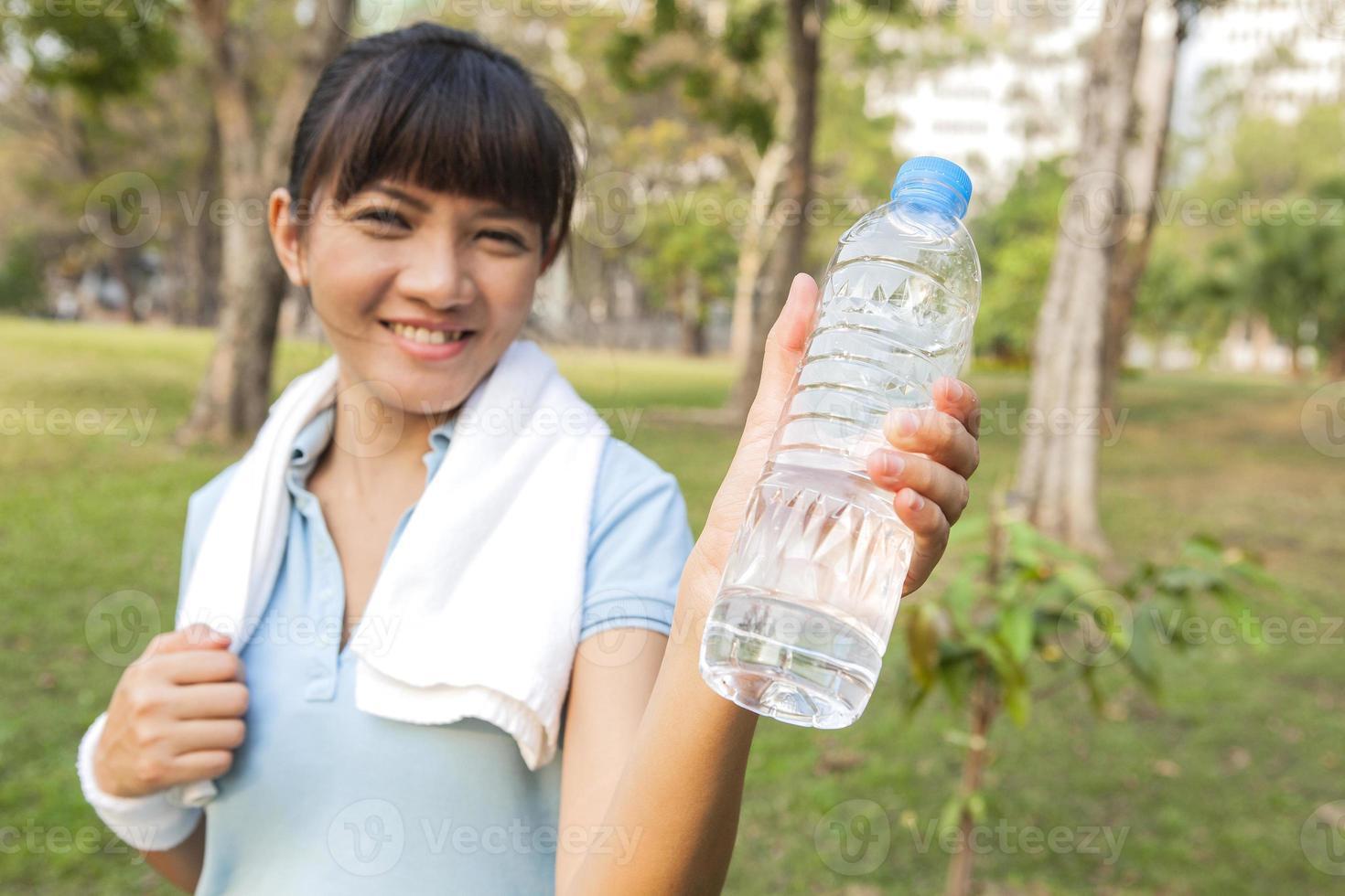 donna asiatica di sport che mostra sorridente bottiglia di acqua foto