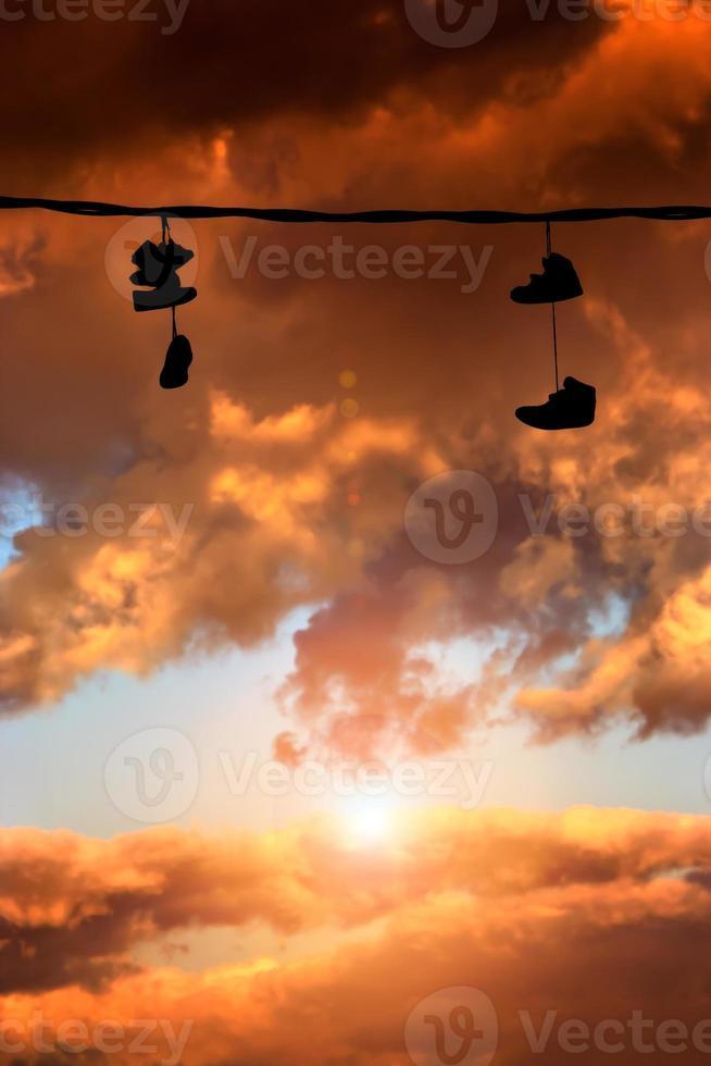 scarpe da ginnastica appese al tramonto foto
