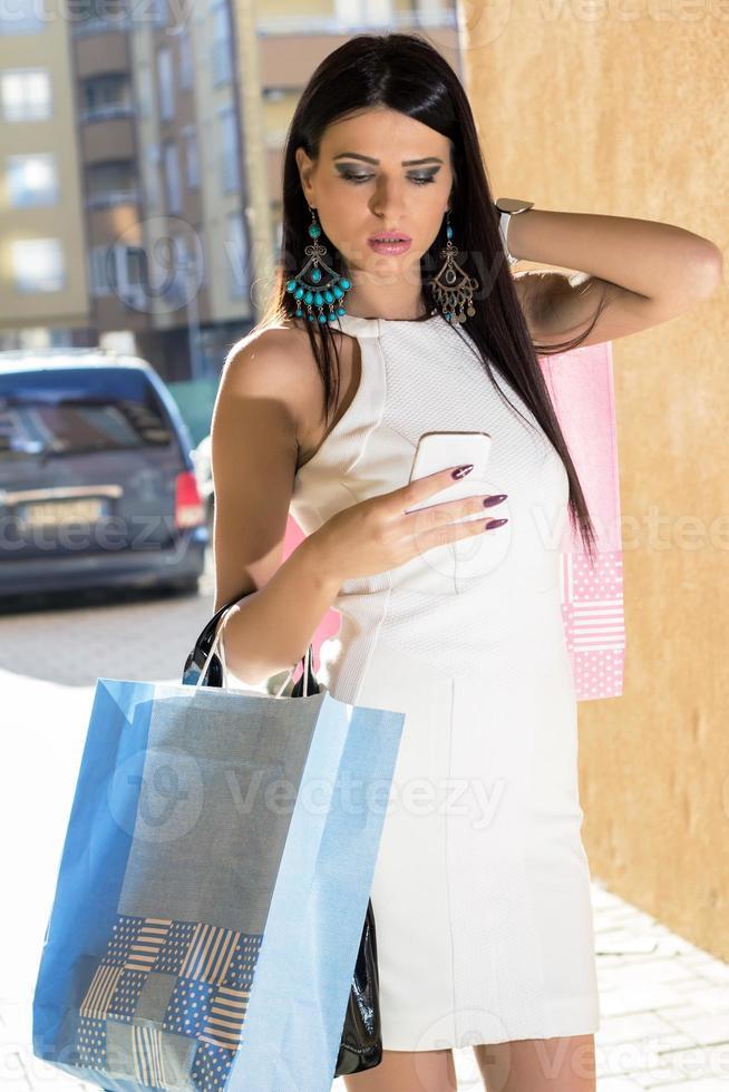 donna dello shopping con il telefono foto