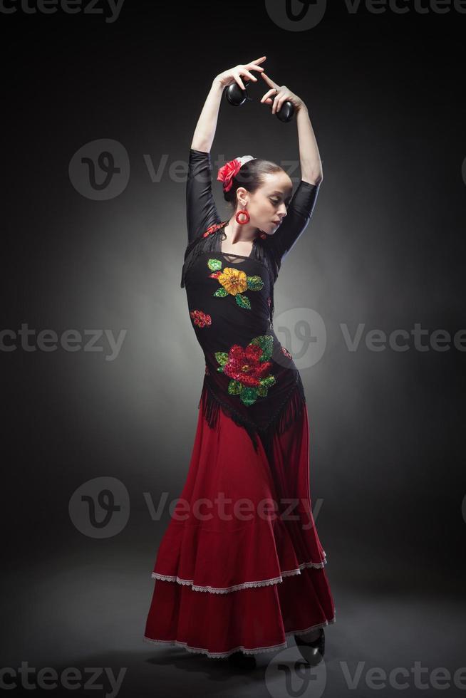 giovane donna che balla il flamenco con le nacchere sul nero foto