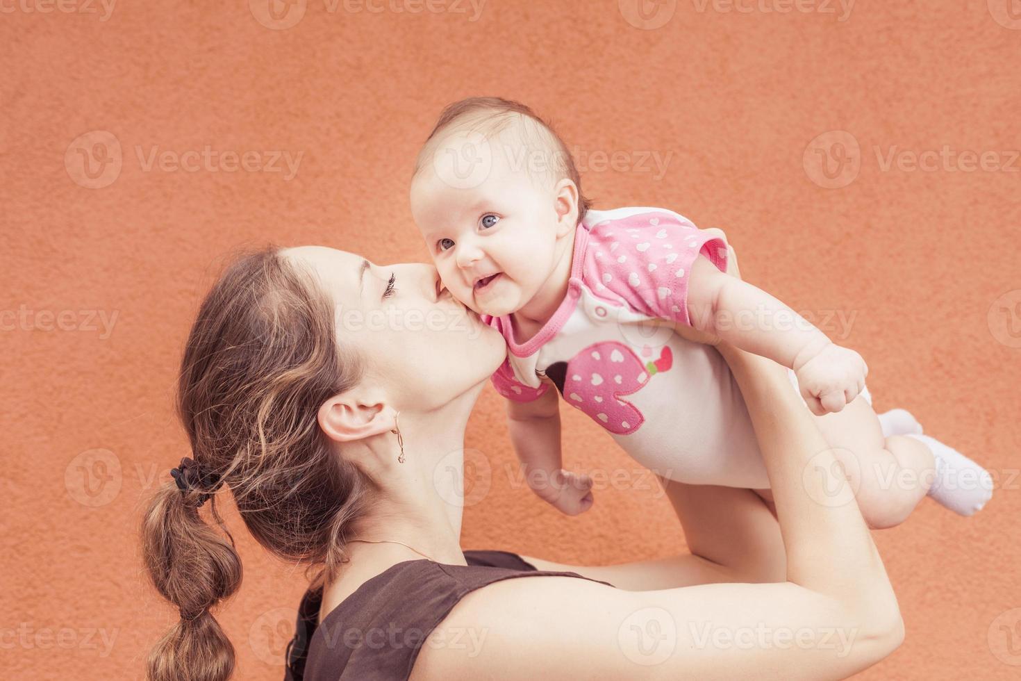 madre felice che bacia il suo bambino a sfondo muro foto