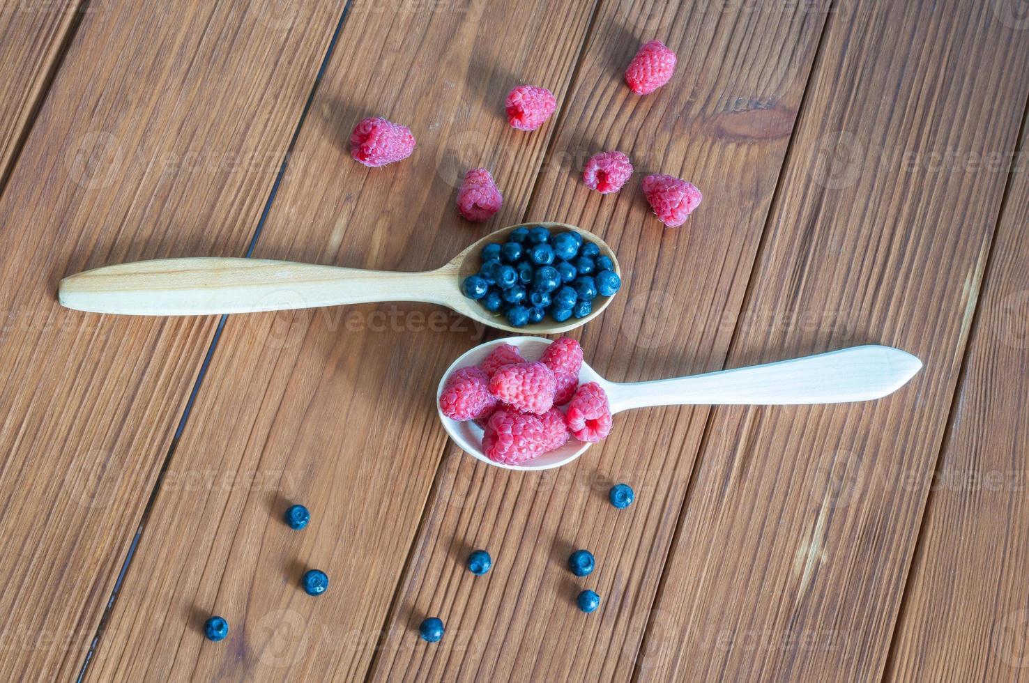 lamponi e mirtilli in cucchiai su fondo in legno. mangiare sano foto