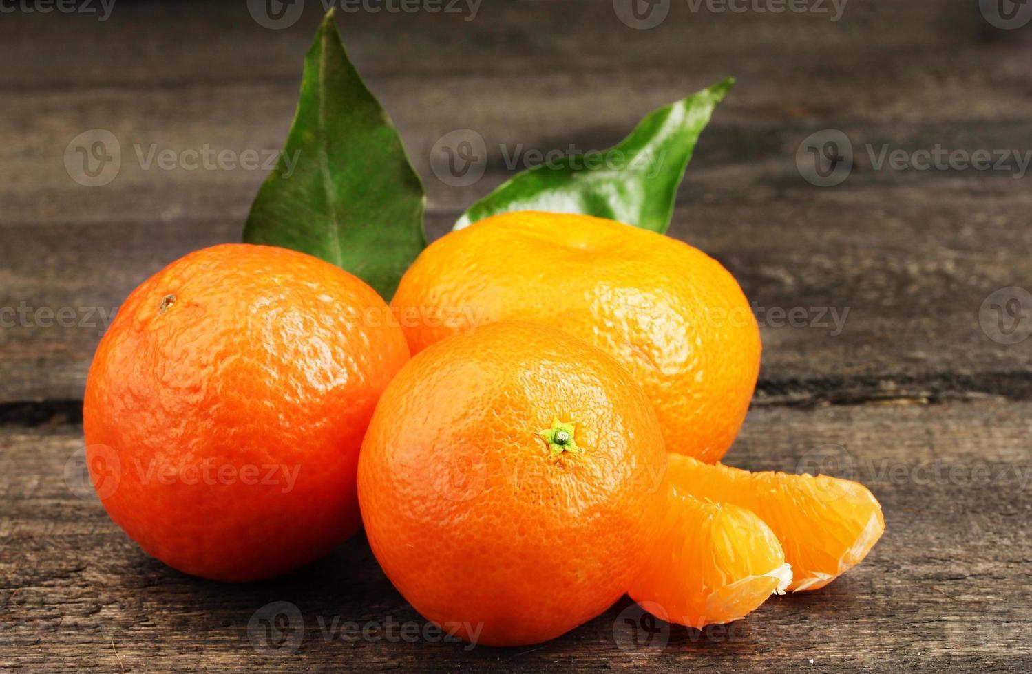 mandarini con foglie sul tavolo grigio in legno foto