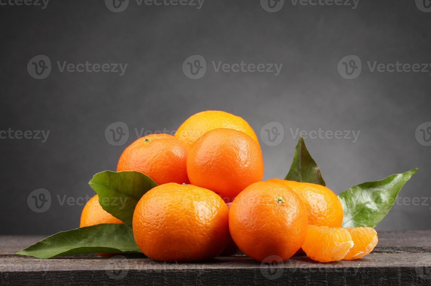 mandarini con foglie sulla tavola di legno su sfondo grigio foto