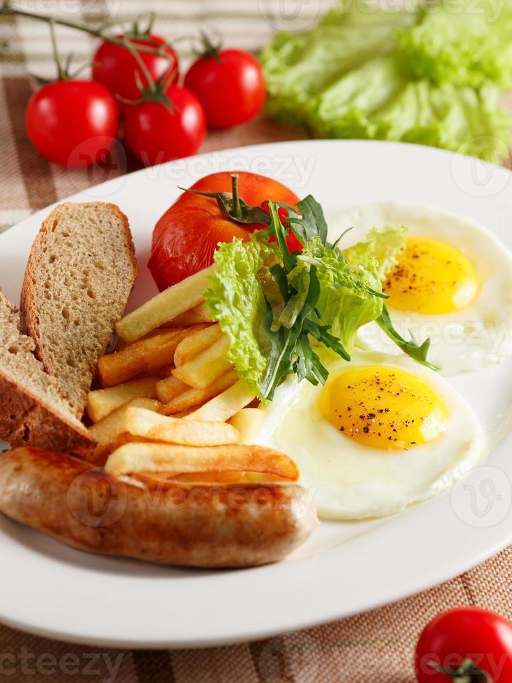 uova fritte con salsiccia e patatine fritte foto