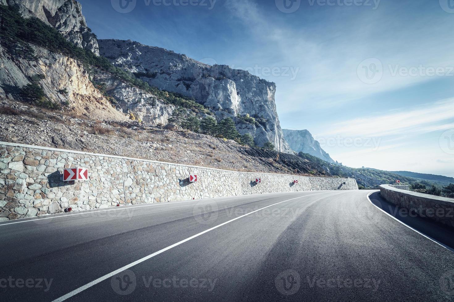 strada asfaltata nella foresta di autunno all'alba. montagne della Crimea foto
