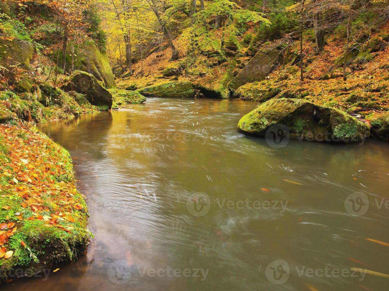 belle linee di fiume autunnali con rocce di arenaria, grandi massi foto