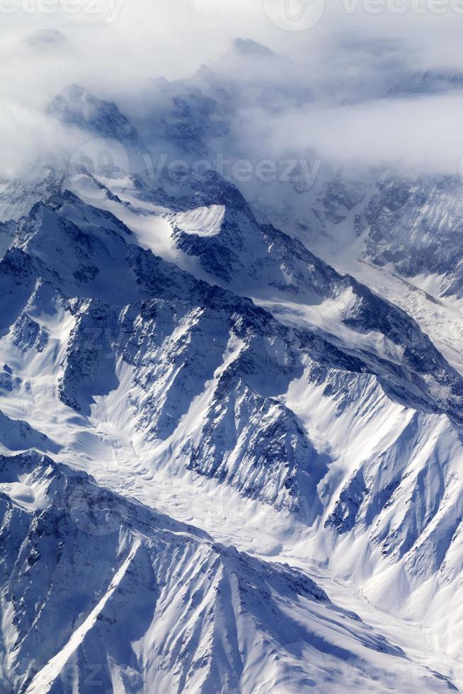 vista dall'alto sulle montagne innevate e sul ghiacciaio nella nebbia foto