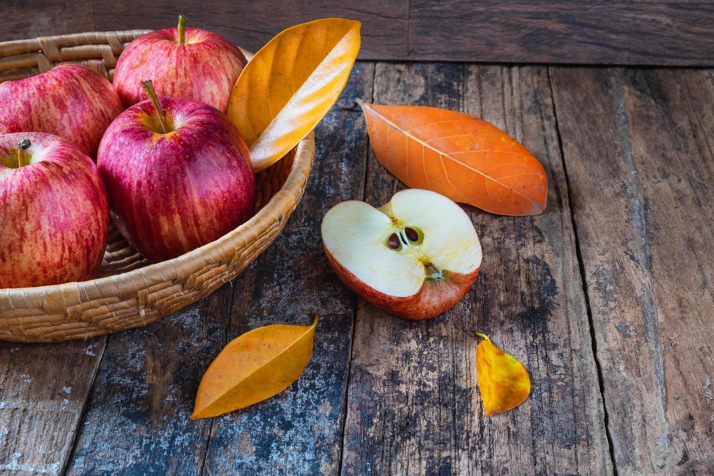 mele rosse su un vecchio tavolo di legno foto