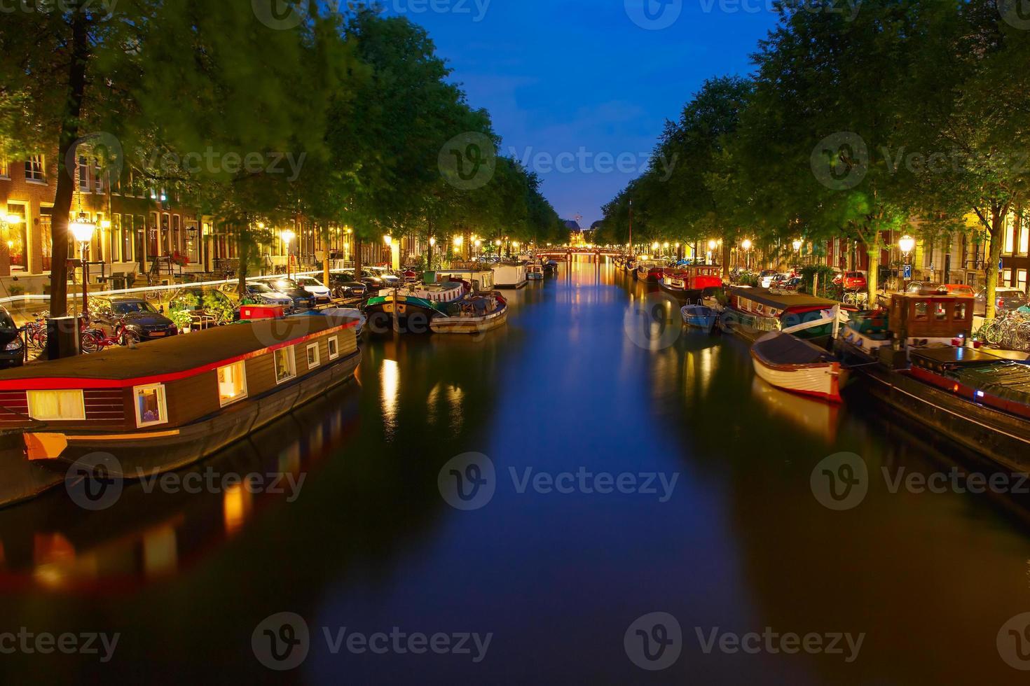 vista sulla città di notte del canale di amsterdam con casa galleggiante foto