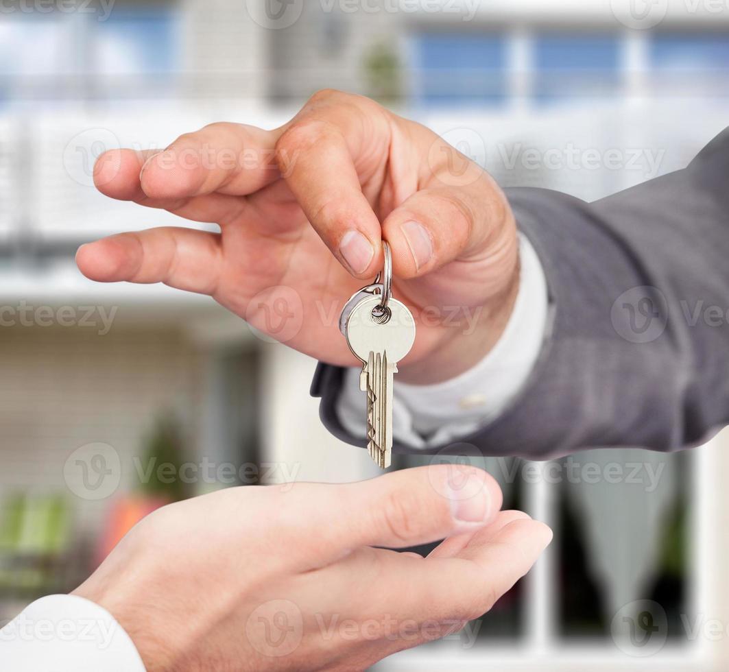 agente immobiliare che dà le chiavi al proprietario contro la nuova casa foto