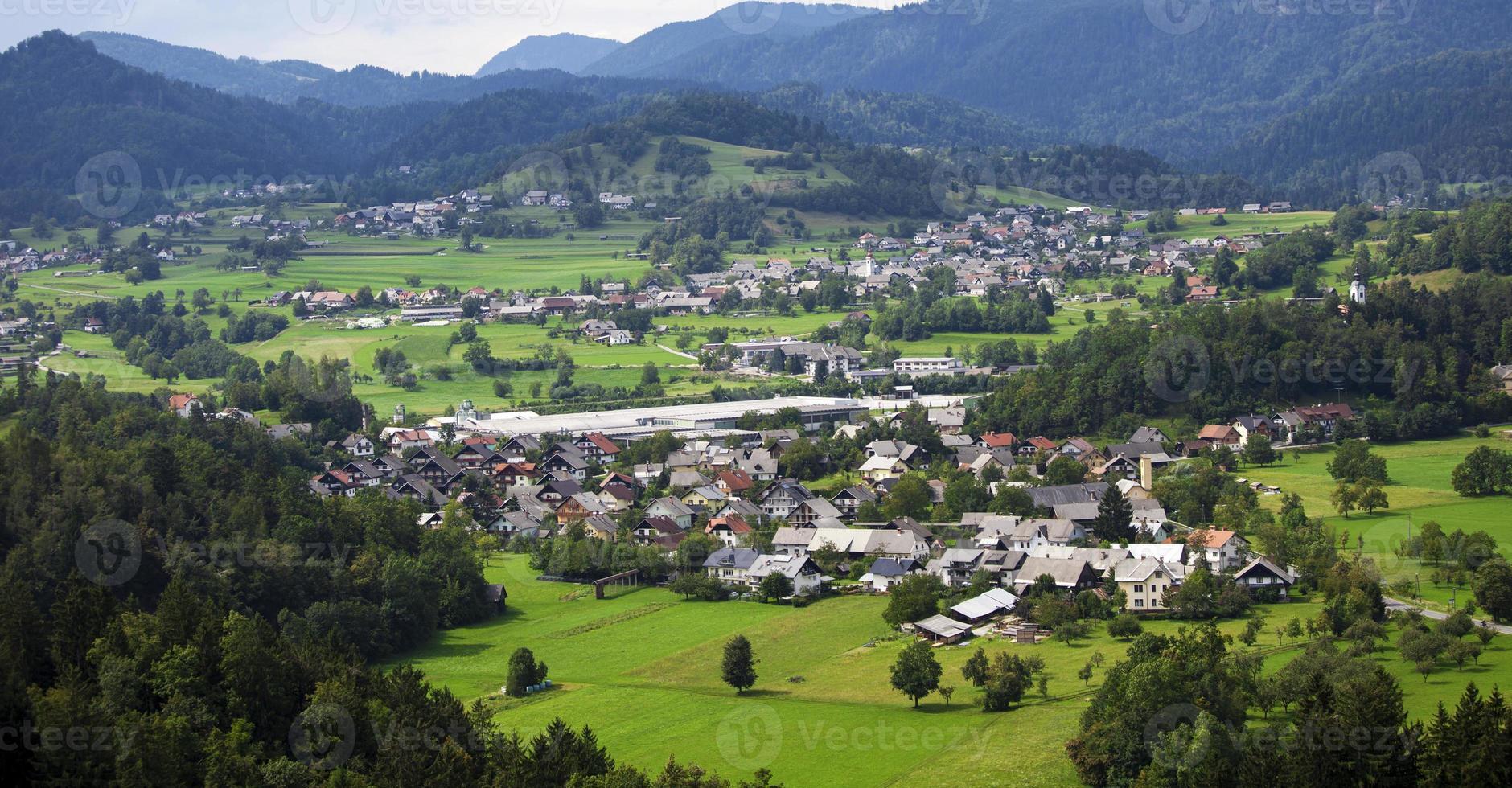 valle di montagna con alberi verdi e case foto