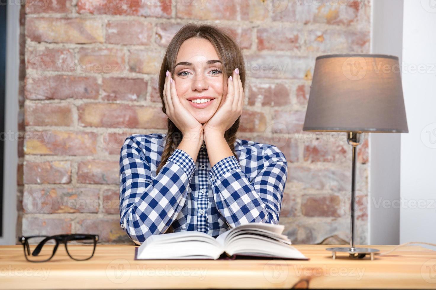 felice bella donna seduta al tavolo con il libro foto