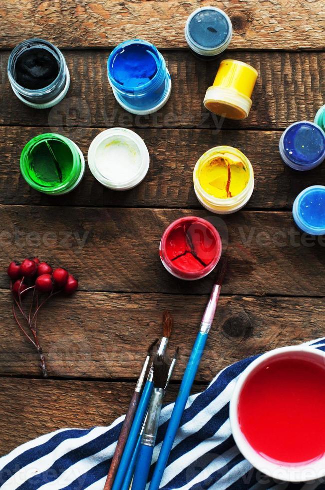 arte della pittura. secchi di vernice su uno sfondo di legno. foto