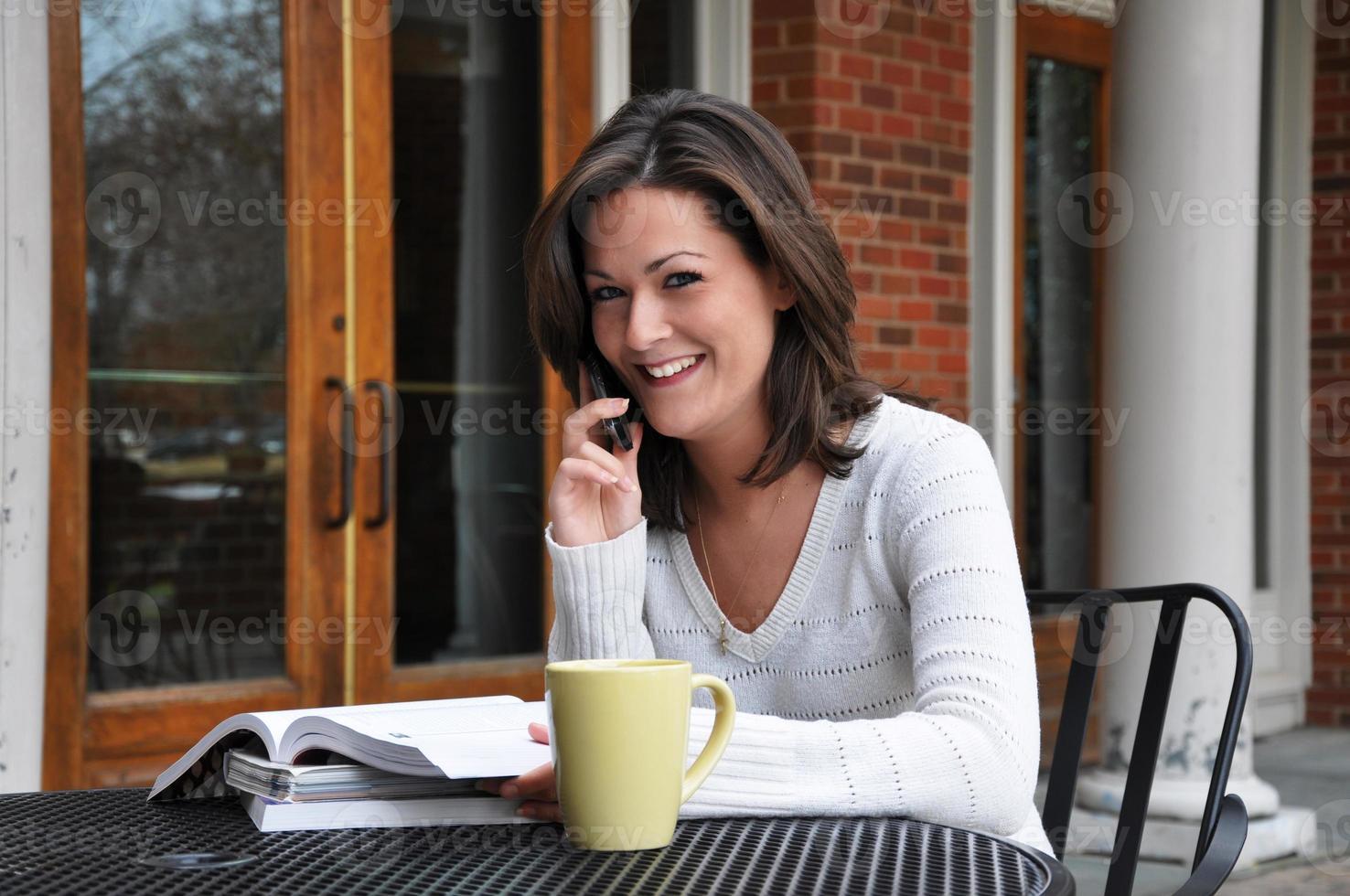 studentessa che studia con libri di testo e telefono cellulare foto