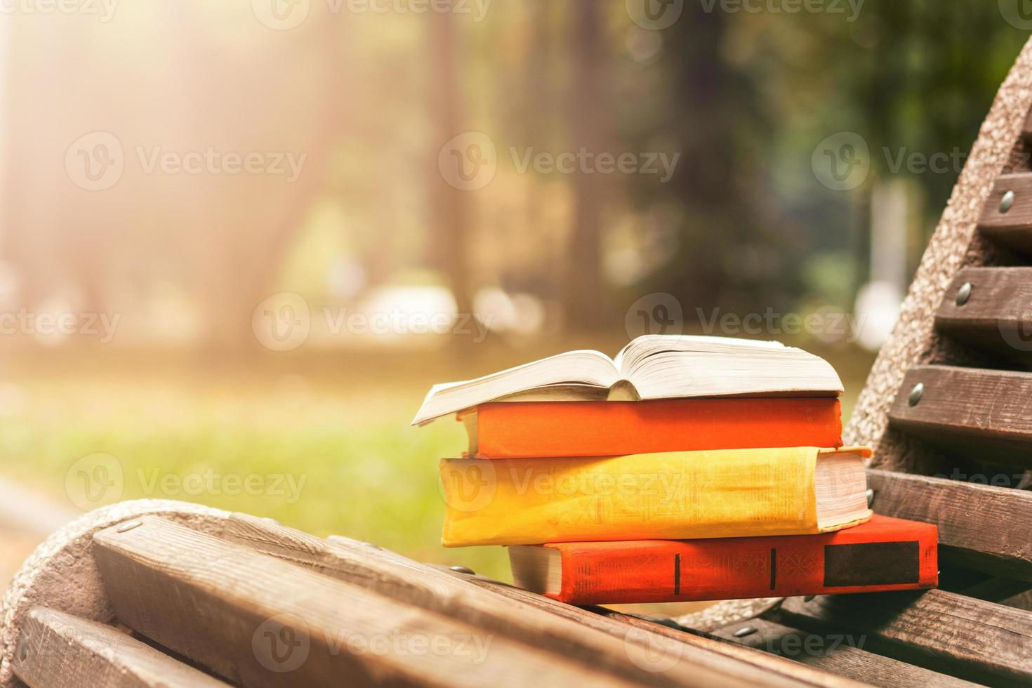 pila di libri con copertina rigida, libro aperto sdraiato su una panchina foto