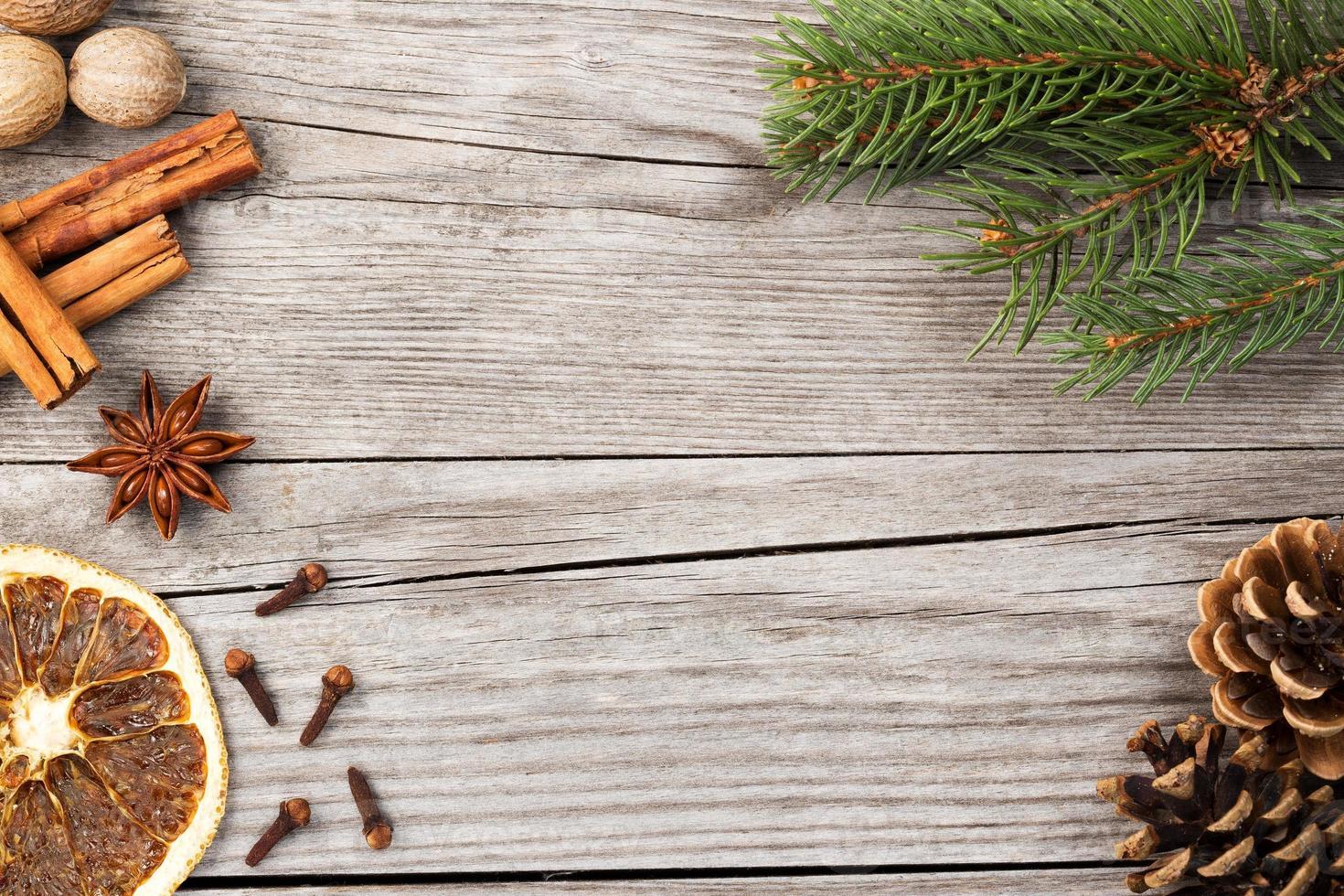 spezie e ramo di abete su fondo in legno foto