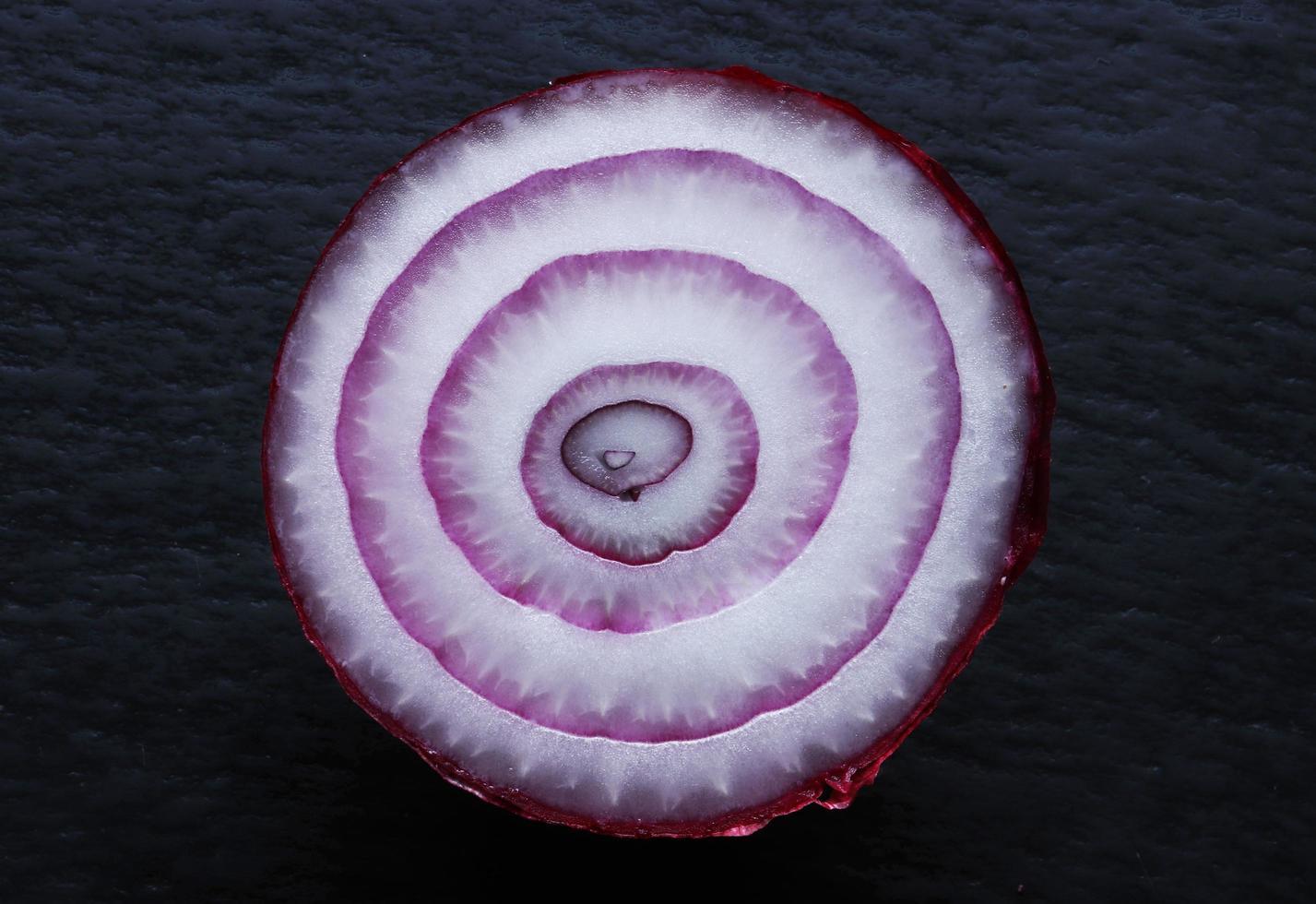 cipolla rossa tagliata a metà su sfondo di ardesia foto