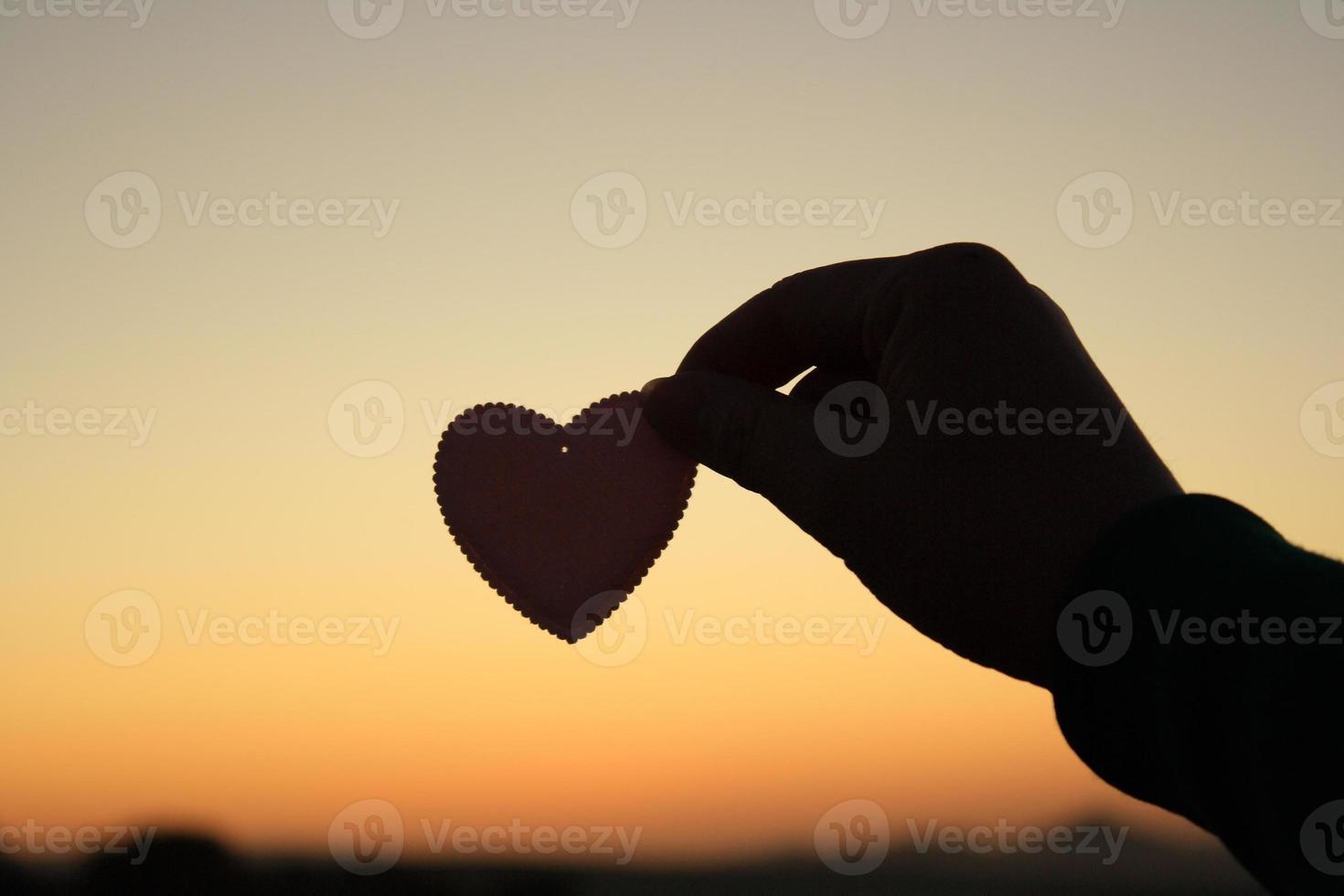 che tiene una silhouette a forma di cuore foto