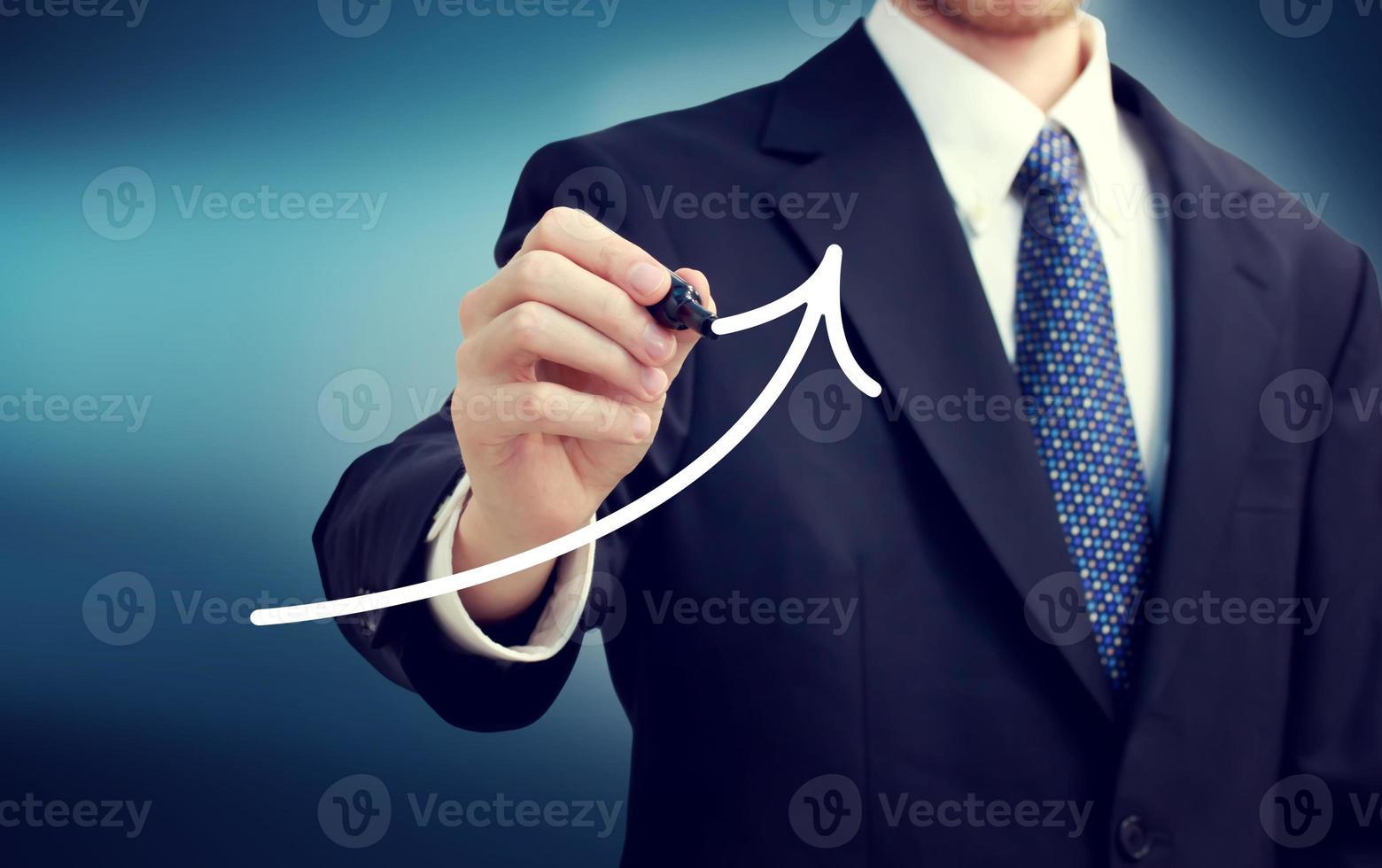 uomo d'affari disegnando una freccia in aumento foto