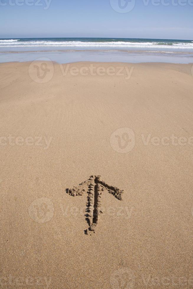 freccia scritta in spiaggia di sabbia foto