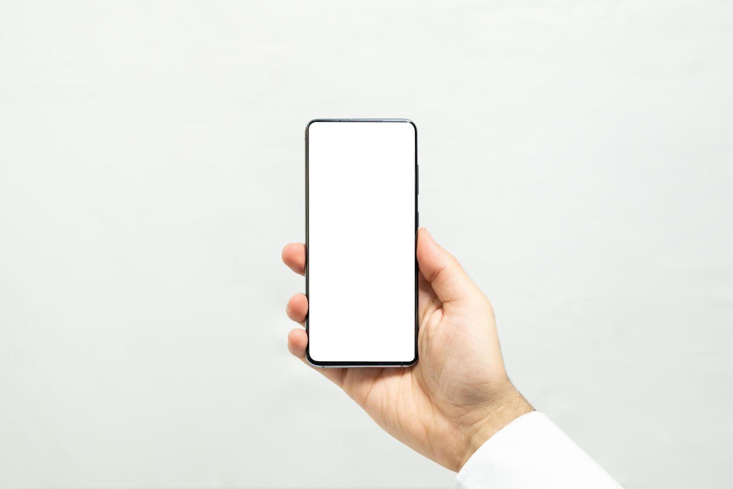 che tiene uno smartphone con schermo bianco verticale foto