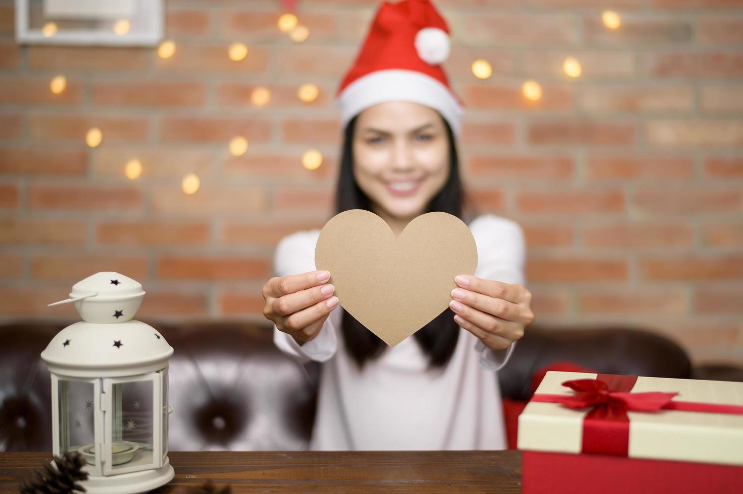 giovane donna sorridente che indossa il cappello rosso di Babbo Natale che mostra un cuore foto
